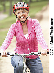 mujer mayor, bicicleta que cabalga, en el estacionamiento