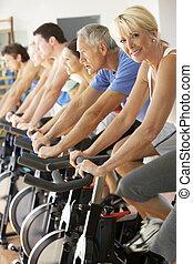 mujer mayor, ciclismo, en, girar, clase, en, gimnasio
