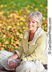 mujer mayor, con, cantimplora, en el estacionamiento
