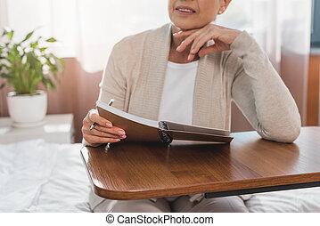 mujer mayor, con, cuaderno, en, hospital