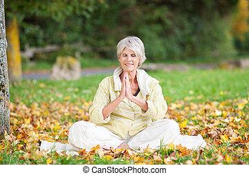 mujer mayor, con, manos agarraron, meditar, en el estacionamiento