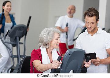 mujer mayor, con, un, personal, amaestrador de la aptitud