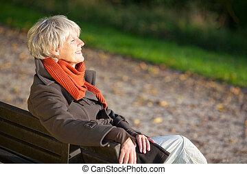 mujer mayor, el gozar, luz del sol, en, banca de parque