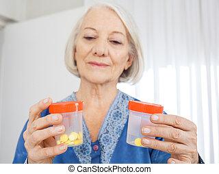 mujer mayor, el mirar, botellas de la píldora