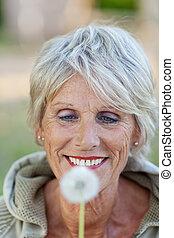 mujer mayor, el mirar, diente de león, en el estacionamiento