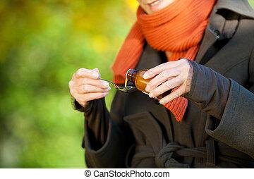mujer mayor, el verter, jarabe, en, cuchara, en, parque
