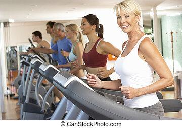 mujer mayor, en, máquina corriente, en, gimnasio