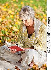 mujer mayor, libro de lectura, en el estacionamiento