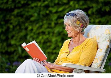 mujer mayor, libro de lectura, en, silla, en, parque