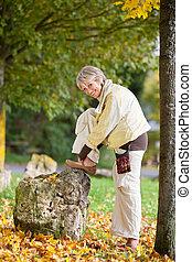 mujer mayor, llevando, zapato, en, otoño, en, parque