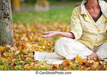 mujer mayor, meditar, en, posición lotus