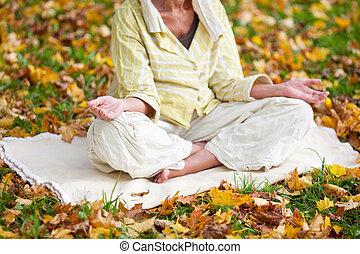 mujer mayor, meditar, en, posición lotus, en, parque