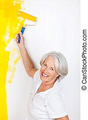 mujer mayor, pared de la pintura, con, rodillo