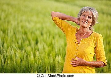 mujer mayor, posar, en, herboso, campo