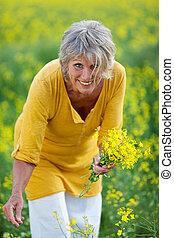 mujer mayor, punteo, flores, en, campo