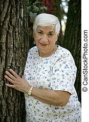 mujer mayor, reclinado, árbol