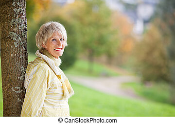 mujer mayor, reclinado, tronco de árbol, en, parque