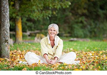 mujer mayor, relajante, en el estacionamiento