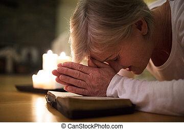 mujer mayor, rezando, manos agarraron, juntos, en, ella, bible.