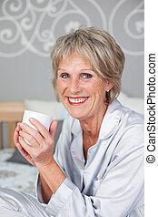 mujer mayor, sostener la taza de café, en, dormitorio