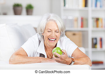 mujer mayor, sujetar una manzana, mientras, mentira en el sofá