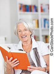 mujer mayor, tenencia, libro, mientras, se sentar sobre sofá