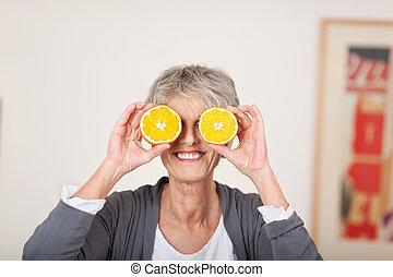 mujer mayor, tenencia, mitad, naranjas, encima, ojos