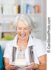mujer mayor, tenencia, pastel, con, encendió velas, en, sofá