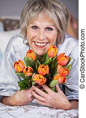 mujer mayor, tenencia, ramo, tulipanes, en cama