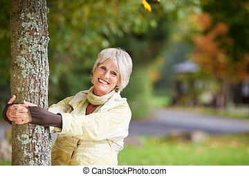mujer mayor, tenencia, tronco de árbol, en el estacionamiento