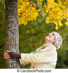 mujer mayor, tenencia, tronco de árbol, mientras, mirar...