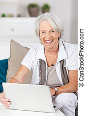 mujer mayor, usar la computadora portátil, mientras, se sentar sobre sofá