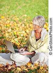 mujer mayor, usar la computadora portátil, mientras, sentado, en el estacionamiento