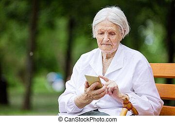 mujer mayor, utilizar, smartphone, mientras, sentar banco