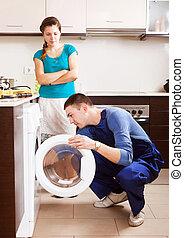 mujer, mirar, como, trabajador, reparación, lavadora