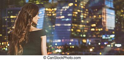 mujer mirar, por la noche, ciudad