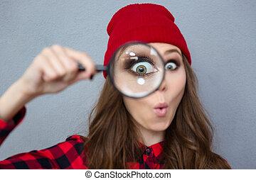 mujer mirar, vidrio, cámara, por, aumentar