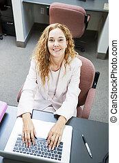 mujer que mecanografía en la computadora portátil, computadora, en el trabajo