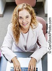 mujer que mecanografía en la computadora portátil, computadora, en, oficina, en el trabajo