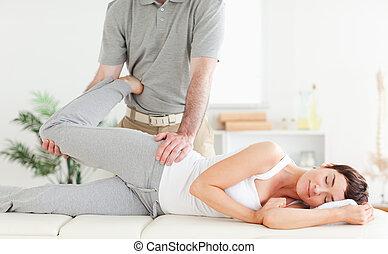 mujer, quiropráctico, estirado, pierna