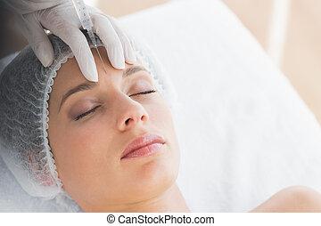 mujer, recieving, inyección de botox, en, frente