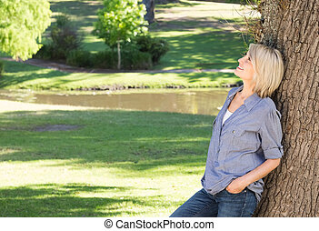 mujer, reclinado, tronco de árbol, en el estacionamiento