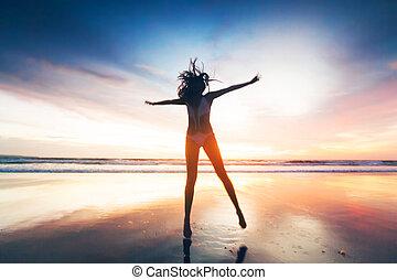 mujer, saltar, en, playa, en, ocaso