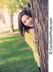 mujer, se esconder atrás, un, árbol