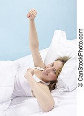 mujer se estirar, en cama