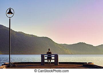 mujer se sentar, en, bench., salida del sol, cerca, ocean., mañana, meditation.