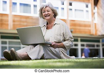 mujer se sentar, en, césped, de, escuela, con, computador portatil