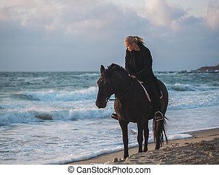 mujer se sentar, en, caballo negro, en el mar, playa