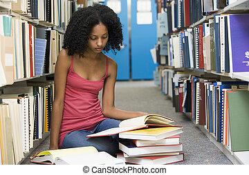 mujer se sentar, en, piso, en, biblioteca, libro de lectura