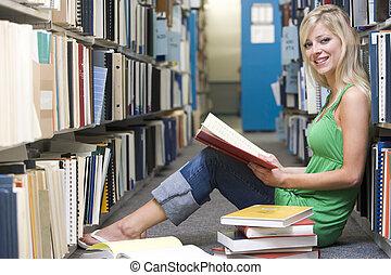 mujer se sentar, en, piso, en, biblioteca, tenencia, libro